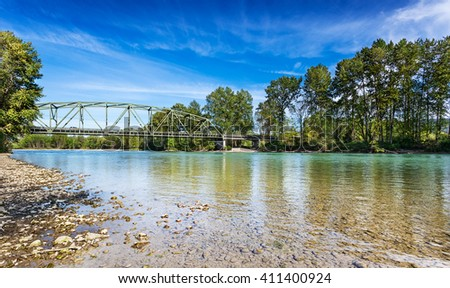 Calm Spring afternoon on the Skykomish River in Monroe, Washington by the Lewis Street bridge. The through truss bridge is state highway 203 - stock photo