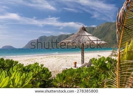 Calm Tropical Beach. Lonely Straw Umbrella on a Tropical Beach on a Con dao Island in Vietnam - stock photo
