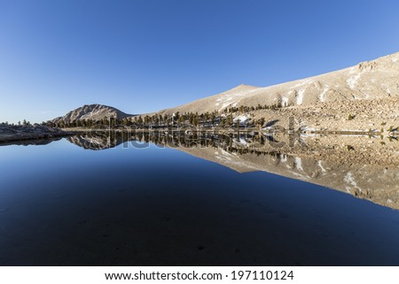 Calm water and mirror like reflection at Cirque lake high in California's Southern Sierra Nevada Mountain Range. - stock photo