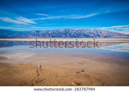 Calm water reflects the mountains and salt flat of Death Valley National Park. - stock photo