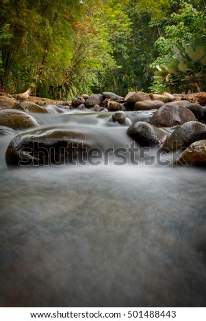 Calm water stream around the rocks - with copy space for text area