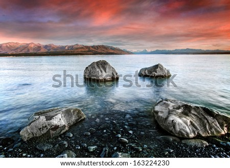calm waters of a glacier lake with mountains behind  - stock photo