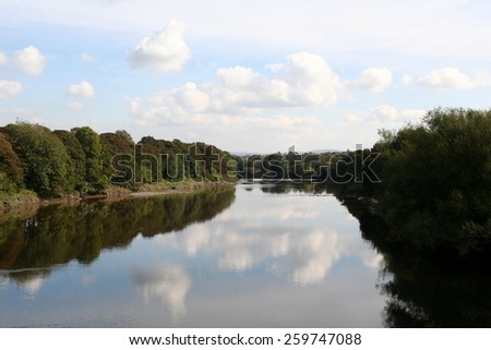 Calm waters of the tree lined River Ribble in Preston, Lancashire, reflecting clouds in the blue sky above. - stock photo