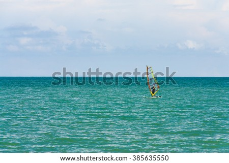 Calm wind surfing with the sun and wind as the driving force on this day. - stock photo