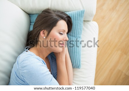 Calm woman lying and sleeping on sofa in the living room - stock photo