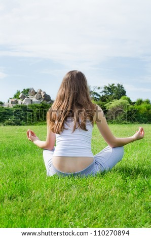 Calm woman meditates on beautiful green lawn in the filds
