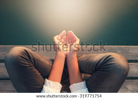 calm woman meditating reciving light energy with hands
