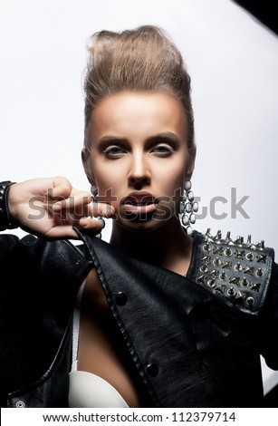 Calm young modern fashion woman punk in black jacket posing