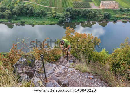 Calmont Climbing, Bremm, Mosel, Germany, september 15, 2013: A male hiker climbs a ladder against the steep slopes