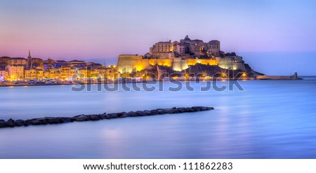 Calvi city illuminated at night with sea in foreground, Corsica Island, France.