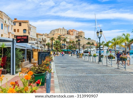 CALVI, CORSICA, FRANCE- AUGUST 18: Street view of Calvi harbour with restaurants, bars and castle on hill, famous landmark of Calvi village on Corsica island, France on August 18, 2015.