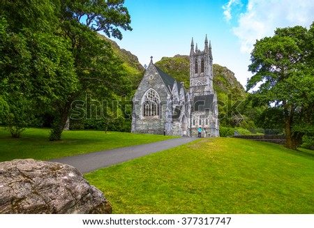 Calway, Ireland - August 4, 2013: Connemara area, visitors in front of the Gothic church of the Kylemore abbey