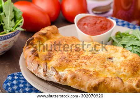 Calzone pizza stuffed with cheese and prosciutto, hot dip and summer lettuce salad - stock photo