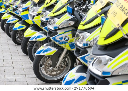 CAMBERLEY, UK - SEPTEMBER 13: Line of BMW motorcycles used by the UK traffic police during the Tour of Britain cycle race in Camberley, UK - September 13, 2014 - stock photo