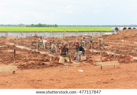 CAMBODIA - SEP,1 : The workers are making the structure of building at the site work near the natural rice field .CAMBODIA SEP,1 2016