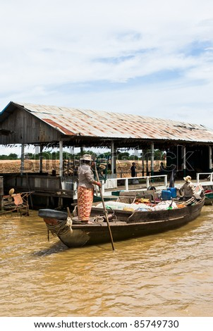 Cambodian women sail on a boat near the fishing village of Tonle sap - stock photo