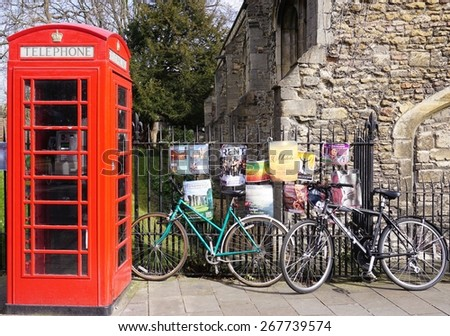 CAMBRIDGE, ENGLAND -12 MARCH 2015- Editorial: Even in the age of cell phones, traditional red British telephone boxes (booths) are still located ubiquitously in the streets of the United Kingdom.