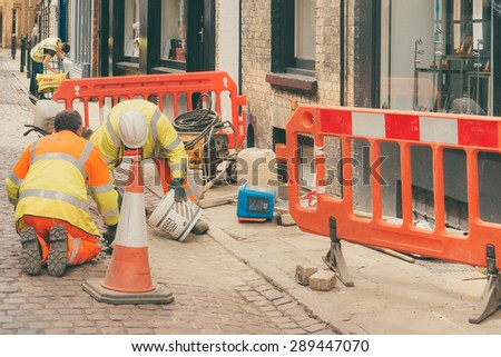 CAMBRIDGE, ENGLAND - 7 MAY 2015: Construction workers on paved street conceptual image of road repairs
