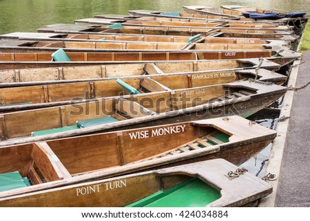 CAMBRIDGE, ENGLAND - MAY 9, 2015:  Flat bottom boats, or punts, with colorful names are commonly used to transport tourists along the River Cam in Cambridge, England.