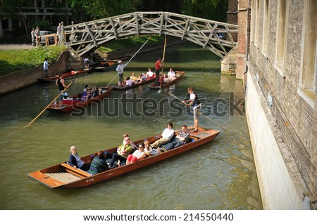 CAMBRIDGE, UK - APRIL 25, 2011: Boats gliding under the Mathematical Bridge across the river Cam in Cambridge, UK - stock photo