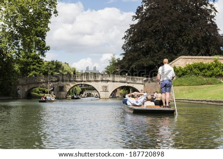 CAMBRIDGE, UK - AUGUST 18: Professional punter in busy River Cam with tree lined bank to one side and the oldest bridge in Cambridge, Claire bridge, in the far horizon. August 18, 2013 in Cambridge. - stock photo