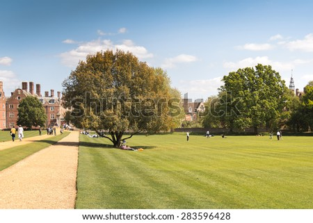 Cambridge, UK - May 16, 2015: St John College (one of University of Cambridge's college) Rear Courtyard with a huge tree and college students relaxing on Weekend. - stock photo