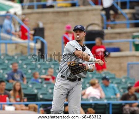 CAMDEN, NJ - AUGUST 15: Bridgeport Bluefish infielder Joe Jiannetti throws the ball to first while blowing a bubble with gum during an Atlantic League baseball game August 15, 2010 in Camden, NJ. - stock photo