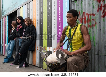 Camden Town, London, UK - April 7, 2007: Three  unidentified girls listen to a street artist playing his drum in a street. Camden, well known for its markets, is visited by 100.000 people each weekend - stock photo