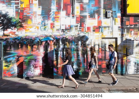 CAMDEN, UK - AUGUST 9, 2015: Young people walk past a colourfully painted wall in Camden Town, London.  - stock photo