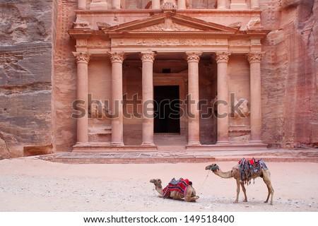 Camels, or rather dromedaries (Camelus dromedarius), waiting for tourists at Al Khazneh (the treasury) 2nd-3d Century AD. Most famous building of the ancient Nabatean city of Petra, Wadi Musa, Jordan. - stock photo