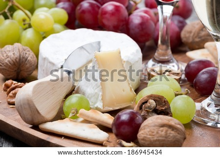Camembert, a glass of red wine, grapes and crackers, close-up, horizontal