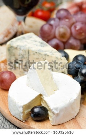 Camembert, blue cheese, grapes and walnuts on wooden board, vertical - stock photo