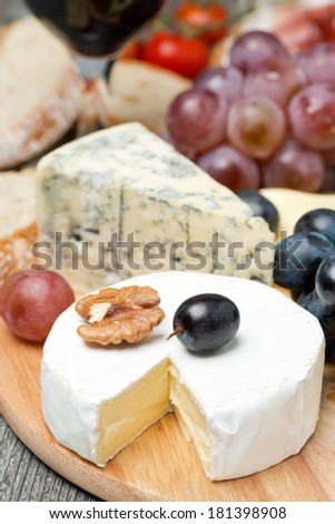 Camembert, blue cheese, grapes and walnuts, vertical - stock photo