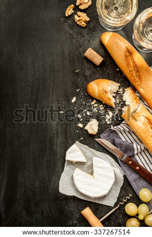 Camembert cheese, baguettes and two glasses of wine on black chalkboard background. Romantic french supper scenery captured from above (top view). Layout with free text space. - stock photo
