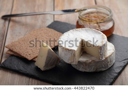 Camembert cheese, jam, and crispbread on a rustic table - stock photo