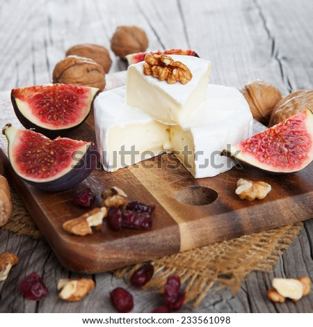 Camembert cheese with figs, nuts and cranberry on dark wooden background - stock photo