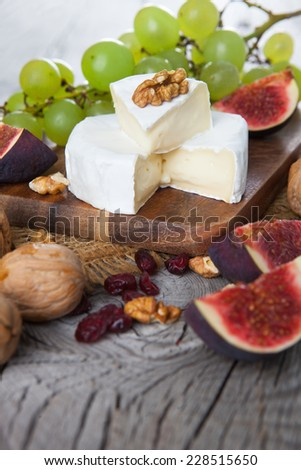 Camembert cheese with figs, nuts and grapes on dark wooden background