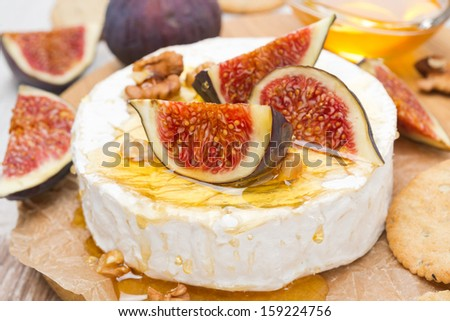 Camembert cheese with honey, figs, walnuts and crackers on a wooden board, close-up, horizontal