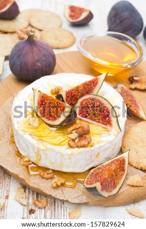 Camembert cheese with honey, figs, walnuts and crackers on a wooden board, vertical - stock photo