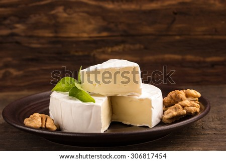 camembert cheese with nuts on a brown plate - stock photo