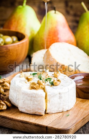Camembert cheese with walnuts,  honey and thyme on rustic table