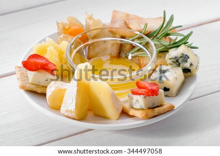 Camembert, Dorblu, Parmesan cheese plate with strawberries, honey and crackers on white table  - stock photo