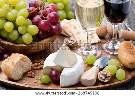 Camembert, fresh baguette, grapes, walnuts and wine on a wooden tray, close-up - stock photo