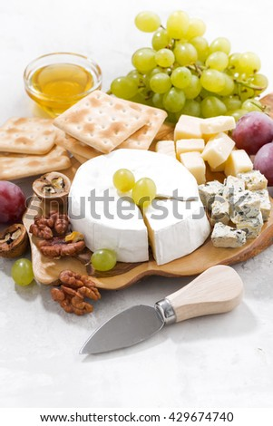 camembert, grapes and crackers on a white table, vertical, closeup