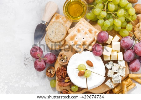 camembert, grapes and snacks on a white background, top view, closeup, horizontal
