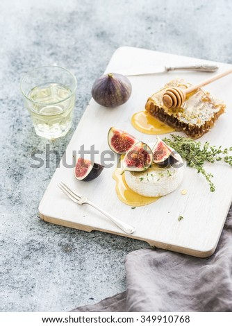 Camembert or brie cheese with fresh figs, honeycomb and glass of white wine on white serving board over grunge rustic grey backdrop, selective focus - stock photo