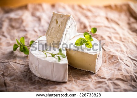 Camembert, soft cheese on crumpled paper background