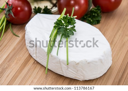 Camembert with fresh Herbs on a cutting board