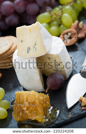 Camembert with fresh honey, grapes and nuts, close-up, vertical