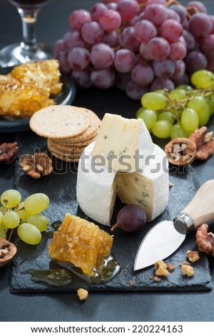 Camembert with fresh honey, grapes and nuts, vertical, top view
